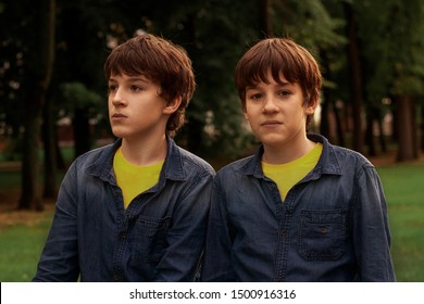 Twins teenagers boys in the park. Transformation from a boy to a man. Transitional age