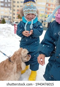 twins in winter overalls hold hands. winter. twins play with dog, spaniel