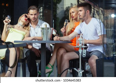 twins women and men relax in shisha cafe outdoor. Celebration, party concept. Friends vapor hookah and drink alcohol in bar lounge. Addiction, bad habits. twins