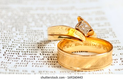 TWINSBURG, OH - JANUARY 14, 2011: Photo of two gold wedding rings resting on the text of Ephesians 5 in the Bible, illustrating the Christian concept of marriage as a picture union with Christ.
