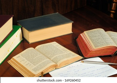 TWINSBURG, OH - JANUARY 16, 2011: Photo of two open Bibles, one in Greek, with other books and study notes, illustrating the concept of researching the original language in Christian Bible study.