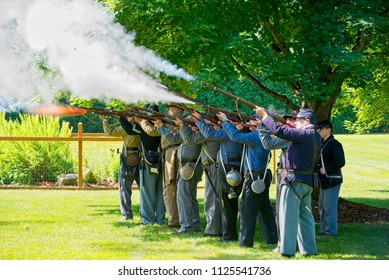 TWINSBURG, OH - JUNE 30, 2018: Civil War reenactors, here representing both Union and Confederate soldiers demonstrate in-line rifle firing during an all-day history event at the public library.