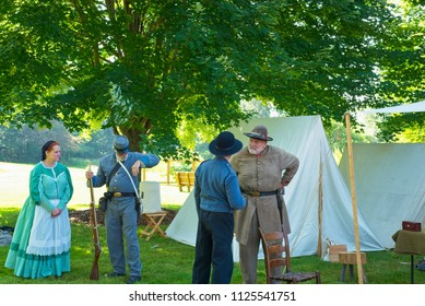 TWINSBURG, OH - JUNE 30, 2018: A group of Civil War reenactors converse by tents and displays in the shade during an all-day history event at the Twinsburg Public Library.