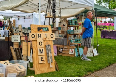 TWINSBURG, OH - JUNE 9, 2018: A visitor waits outside the Ohio Home craft booth at A Taste of Twinsburg, an outdoor culinary and arts festival held one Saturday in summer on the town square.