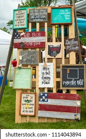 TWINSBURG, OH - JUNE 9, 2018: A display of inspirational plaques is part of a vendor booth at A Taste of Twinsburg, a culinary and arts and crafts festival held on the town square.