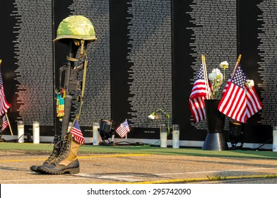 TWINSBURG, OH, USA - JULY 4, 2015: A fallen soldier tribute stands before panels of a replica Vietnam Memorial Wall, on tour with the Cost of Freedom tribute, a traveling veterans-based exhibit