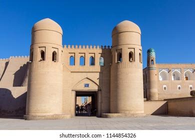Twin-turreted West Gate with Madrassah of Muhammad Amin-khan in background - Khiva, Uzbekistan