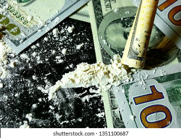 Twisted banknote through which sniffing cocaine. A hundred dollars bills and a lot cocaine scattered on the table. Illegal drugs and dirty money. Addict use Drugs. Breaking the law, drug addiction.