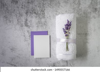 Twisted bath towel with lavender and blank card on light gray background. Minimalism, soft focus, copy space. SPA concept.