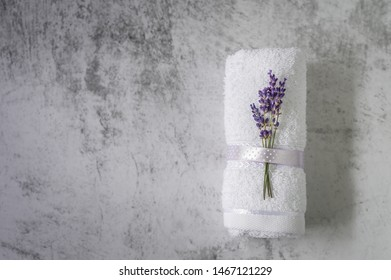 Twisted bath towel with lavender on light gray background. Minimalism, soft focus, copy space. SPA concept.