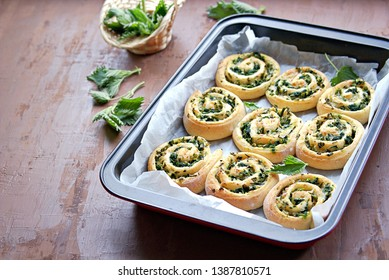 Twisted homemade yeast buns with nettles, green onions, cheese and egg. Copy space.