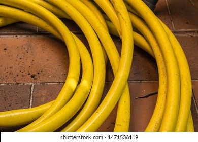 Twisted hosepipe on the brick floor, yellow garden hose closeup - Image