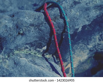 Twisted nylon green and red ropes. Detail of old used rope on sandstone rock.
