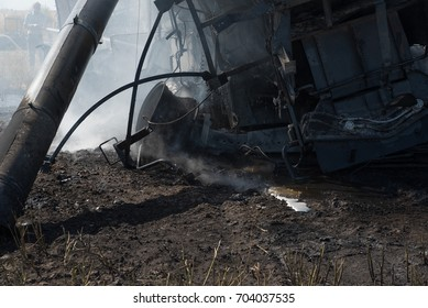 The twisted remains of a burned out combine with a volunteer fire fighter in the background
