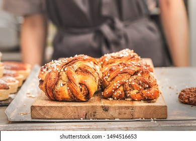 Twisted traditional Swedish cinnamon rolls  at a café. The sweet buns are on a wooden chopping board, and there is an  unrecognizable person wearing an apron in the background.