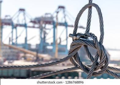Twisted wire rope knot closeup with blurred industrial landscape of port pier on background. TIS cargo terminal in largest port of Ukraine. Industrial backdrop. Grunge steel wire rope texture closeup