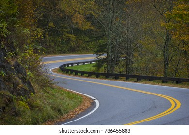 Twisting curvy road winding through fall colorful trees in national park with long exposure car streaks showing motion speed and transportation