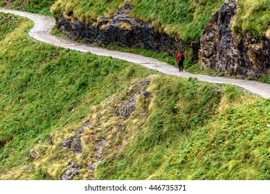 Twisting mountain path with a lone trekker
