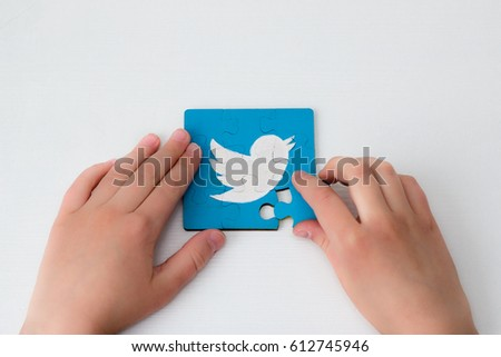 Twitter logo on puzzle.  Hands. Social network. Handmade. Acril painted. Minsk, Belarus - February 26, 2017.