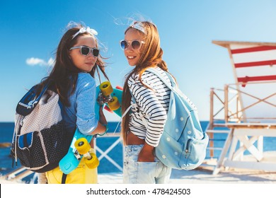 Two 10 years old children wearing cool clothing and backpacks posing with colorful skateboards on the beach, urban style, pre teen summer fashion.