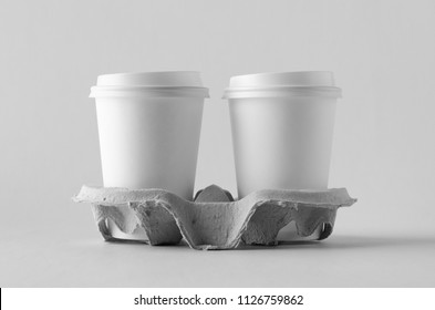 Two 12 oz. white coffee paper cups with lid in a holder. Blank Mock-Up.