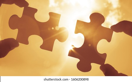 two 2 hands trying to connect couple puzzle piece with sunset background. Jigsaw alone wooden puzzle against sun rays. one part of whole. symbol of association and connection. business strategy