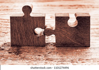 two 2 wooden puzzle stand on wood table
