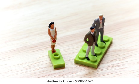 The concept of gender discrimination. Two miniature men and a miniature woman standing on a block of different size.