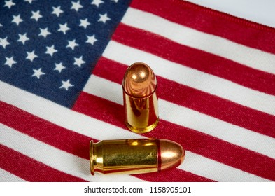 Two .45 caliber bullets laying on an American Flag