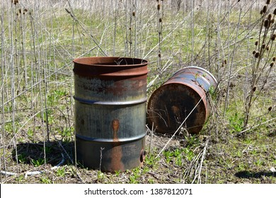 Two 55 gallon steel drums rotting away in a overgrowth area.