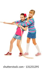 Two 9-10 years old girls pulling the rope in team standing isolated on white