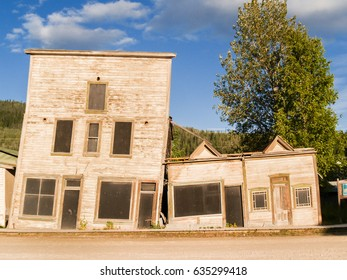 Two abandoned buildings collapsing together due to cahnges in permafrost underground