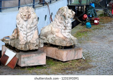 Two abandoned stone lions on a quayside in Amsterdam