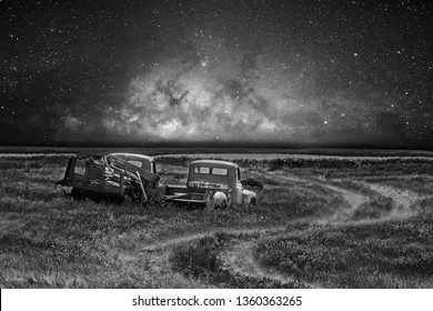Two abandoned vintage trucks parked beside a trail in a field under a star filled sky in a rural countryside landscape