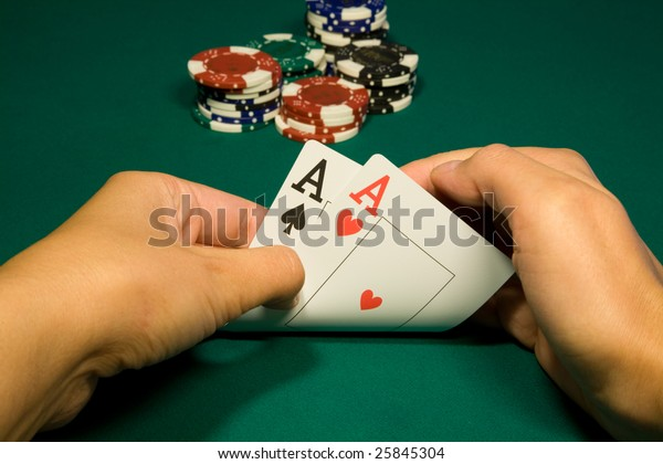 Two aces in hand in game poker on the green casino table