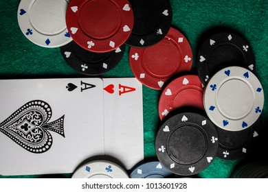 two aces in the hands of a close-up. An concept Image of a poker table. two aces, two playing cards and poker chips on the green casino table / on a black background. success in gambling. soft focus
