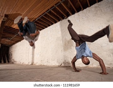 Two acrobatic capoeria artists do headstands and backflips