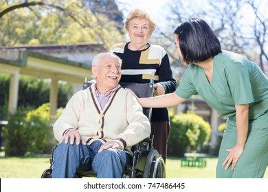 Two active elderly people outdoor with asian nurse.