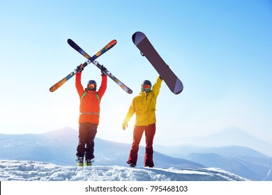 Two active friends skier and snowboarder are standing on mountain top against blue sky and mountains. Ski resort concept