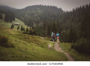 Two active girls hike up a grassy mountain overlooking the spectacular green valley. Breathtaking mountain range surrounds females trekkers ascending a grassy hill to the woody house.