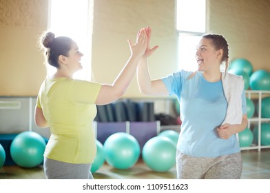 Two active oversized women making high five after successful training in gym
