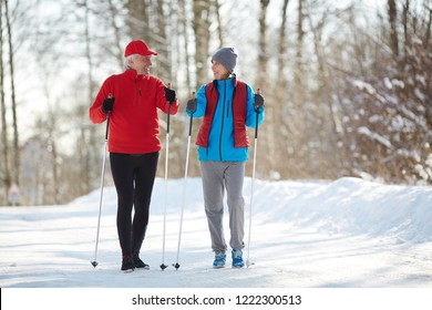 Two active seniors in sportswear trekking down forest road on frosty winter day