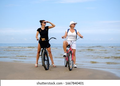 Two active women, senior and middle age on bikes with toy terrier dog looking aside. Sea or ocean and sky on background. Concept of lifestyle, leisure, sport. Copy-space place for ad text.
