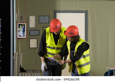 Two actors men in suits and construction workers in hard hats playing the role on stage