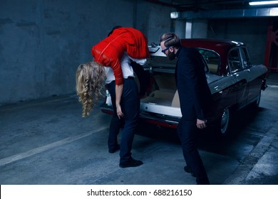 Two actors plays kidnapping kidnap a young long haired blonde model, holding her on the shoulder and puts her inside in a car trunk of a vintage car at the dark underground parking. Horizontal view.