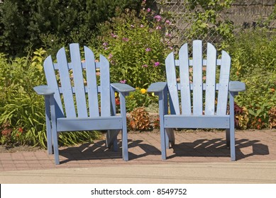 Two adirondack blue chairs in a New England garden