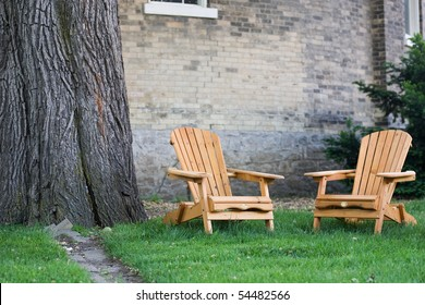 Two adirondack chairs beside a huge tree trunk, with a brick building in the background