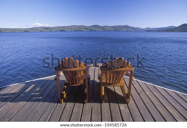 Two Adirondack chairs on a deck overlooking Lake George, NY