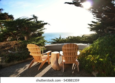 Two Adirondack chairs on a porch overlooking the ocean