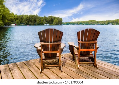 Two Adirondack chairs on a wooden dock overlooking a calm lake. Cottages nestled between green trees are visible across the water.